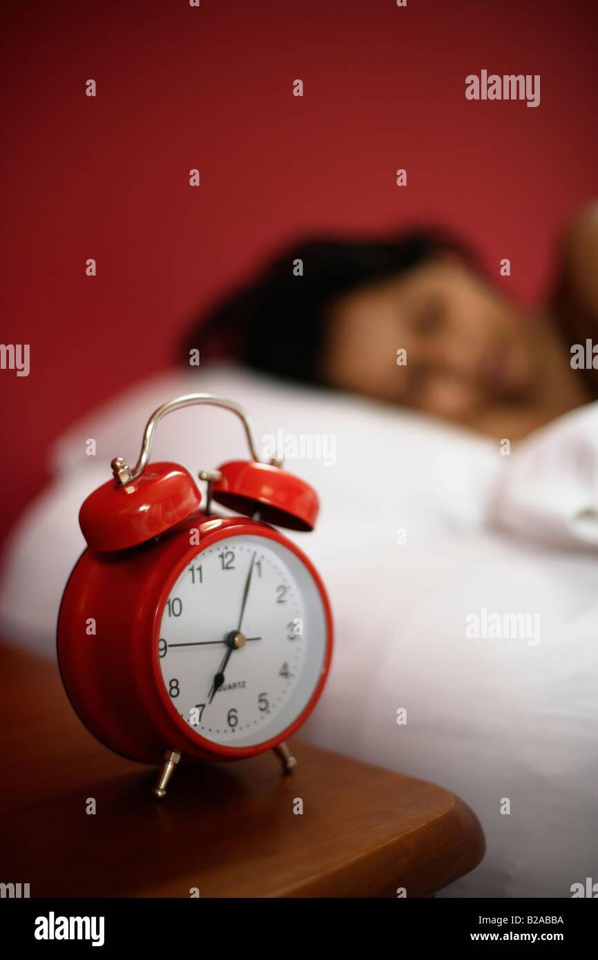 Indische Frau 30er Jahre schläft neben Wecker Stockbild