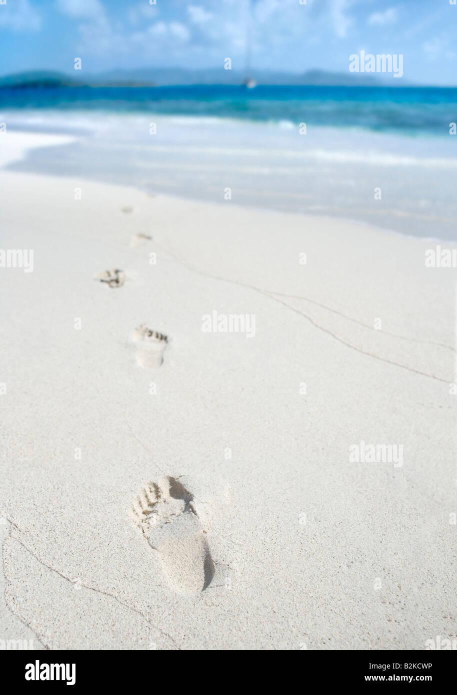 Fußabdrücke auf einem sonnigen tropischen Strand in der Karibik Stockbild