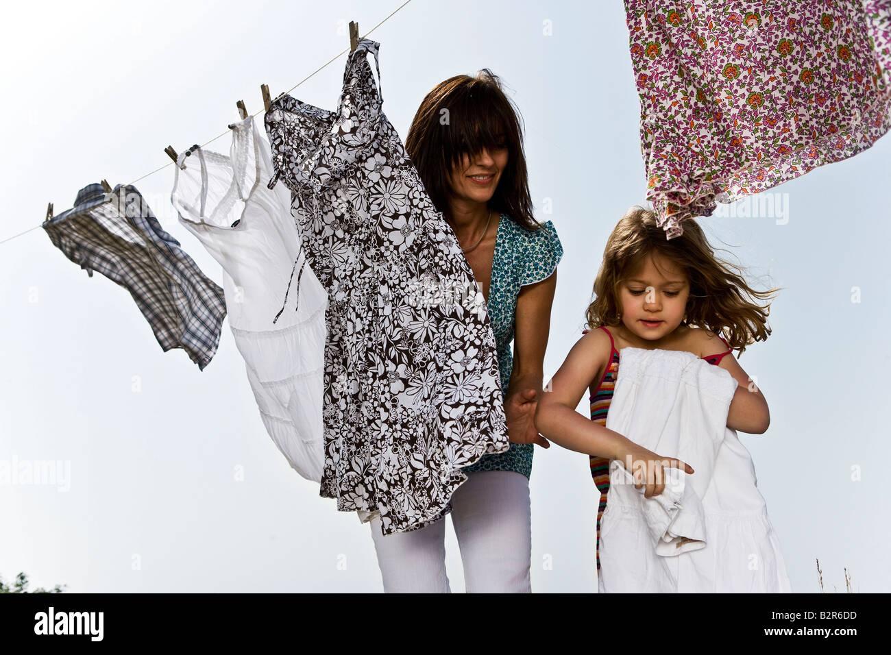 Hilft Mutter Falten Kleidung Mädchen Stockbild