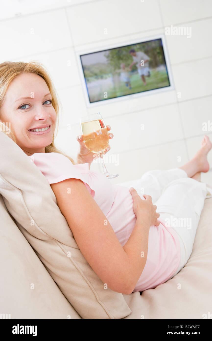 Schwangere Frau vor dem Fernseher mit Glas weißen Wein lächelnd Stockbild