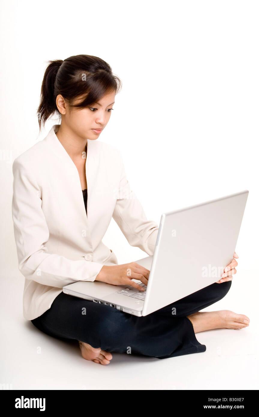 eine s e asiatische gesch ftsfrau sitzt auf dem boden mit ihrem laptopcomputer stockfoto bild. Black Bedroom Furniture Sets. Home Design Ideas