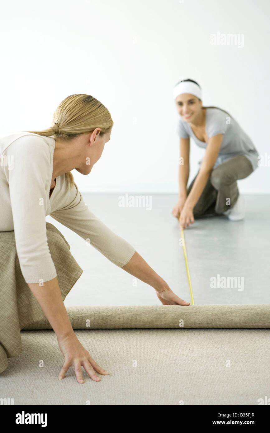 Mutter und Tochter Teppich zusammen installieren Stockbild