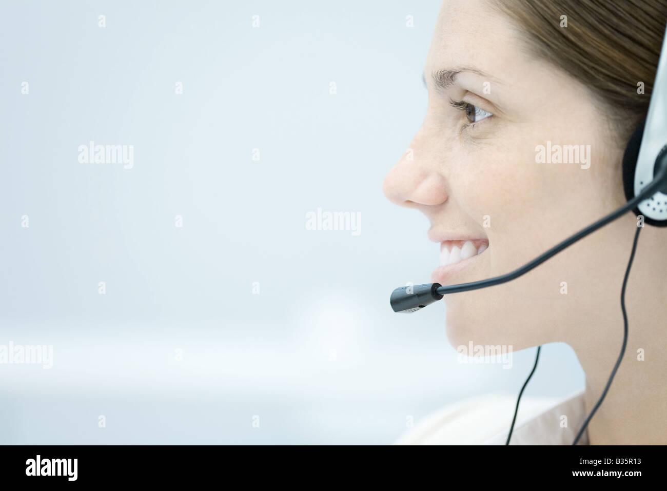 Junge Frau trägt Kopfhörer, schauen weg und lächelnd, Seitenansicht Stockbild