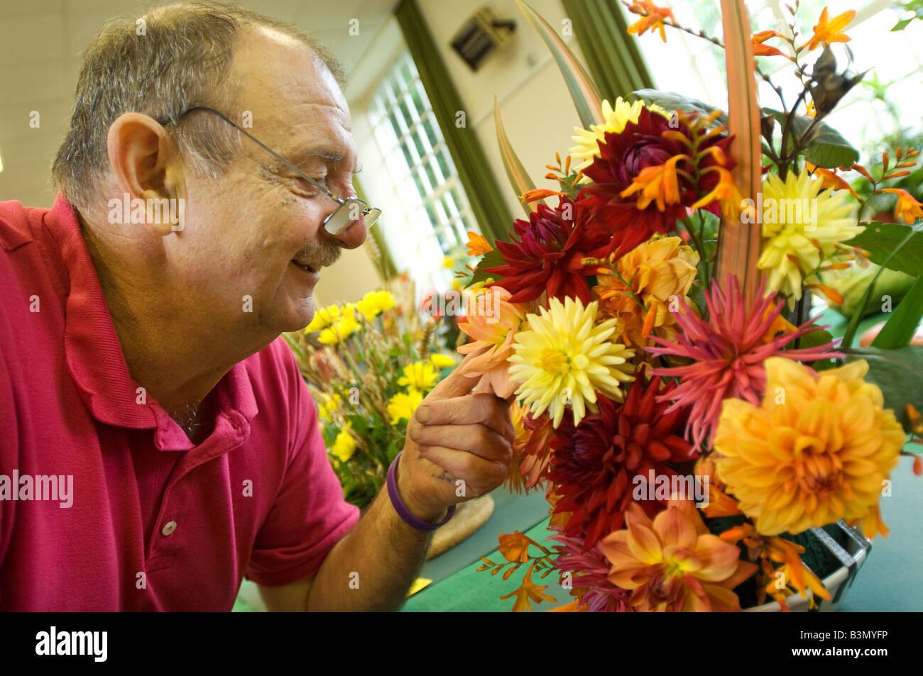 Ein älterer Mann, genießen Sie einen preiswerten Tagesausflug bewundern die Dahlie Einträge in einem Stockbild