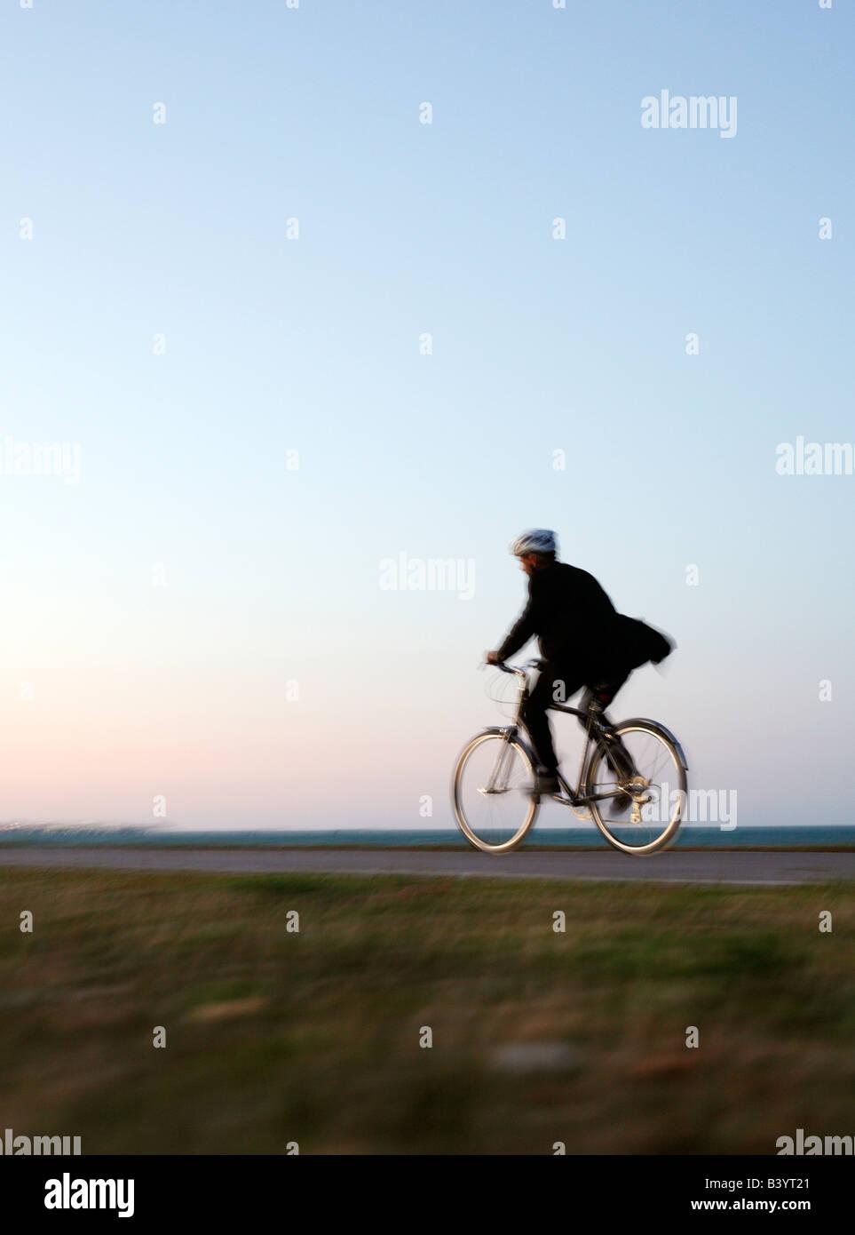 Mann im Anzug mit Fahrrad entlang der Seepromenade in Chicago in der Abenddämmerung (gesunder Lebensstil) Stockbild