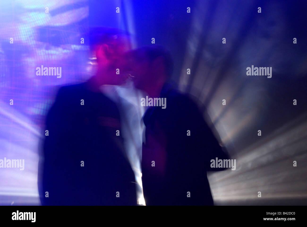 verschwommene Aufnahme zweier Männer, die Auseinandersetzung im Gespräch im Club mit Stroboskoplicht Hintergrundbeleuchtung Stockbild