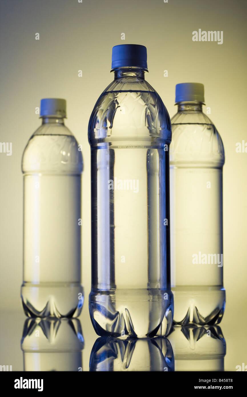 Drei Plastikwasserflaschen h2o im Studio weißen Hintergrund mit gelben Gel vertikal. Stockbild
