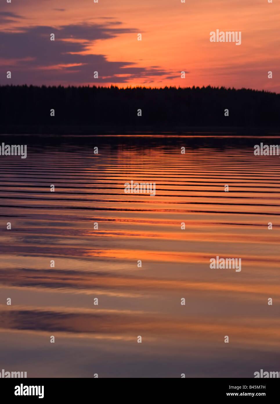 Abstraktion Bild: Wellen auf dem Wasser der ruhigen Waldsee im Sonnenuntergang Hintergrund weiße Nacht Stockbild