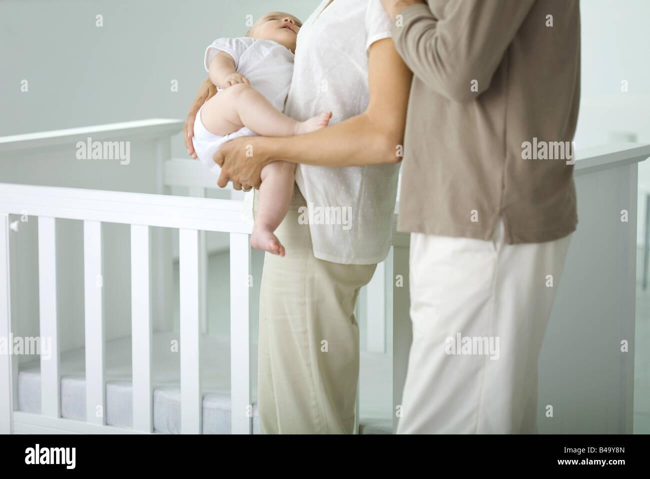 Eltern stehen neben Krippe im Kindergarten, beschnitten Mutter hält schlafen Baby, Ansicht Stockbild