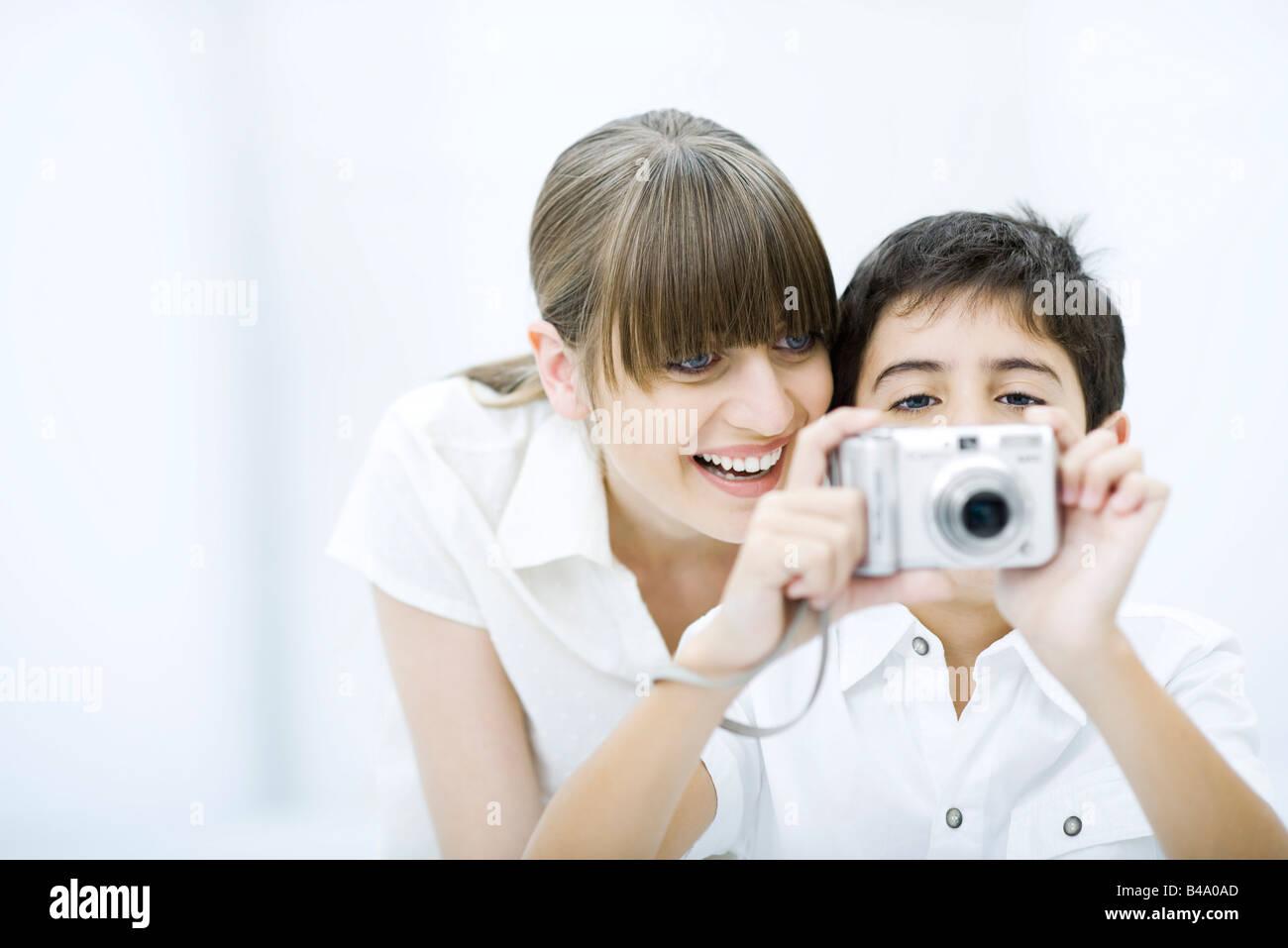 Junge lächelnd unter Bild mit Kamera, Mutter beugte sich über seine Schulter Stockbild