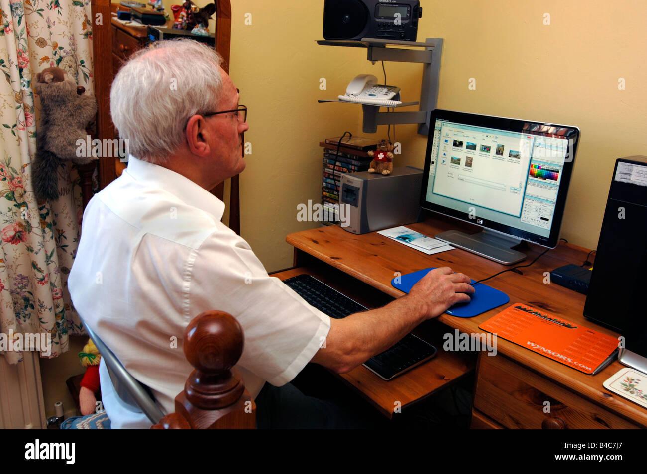Pensionierter Mann zu Hause mit Hilfe eines Computers Stockbild