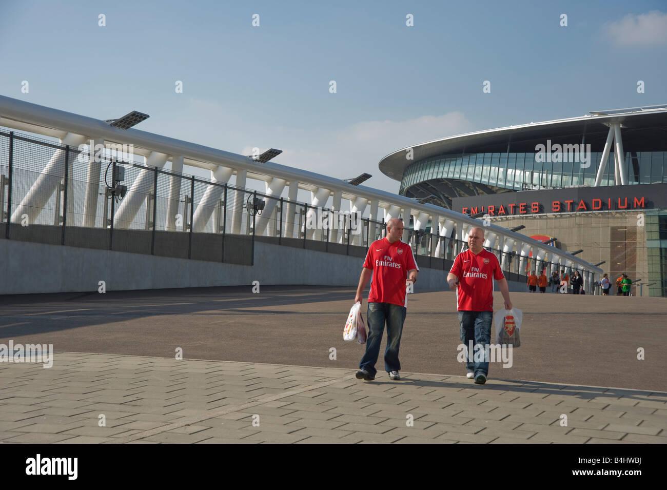 Zwei Arsenal-Fans Arsenal Hemden und Arsenal Träger Tragetaschen. Stockbild