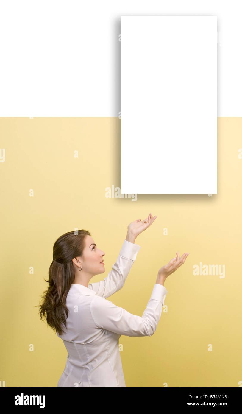 Frau zeigt leere weiße Bild an Wand Stockbild