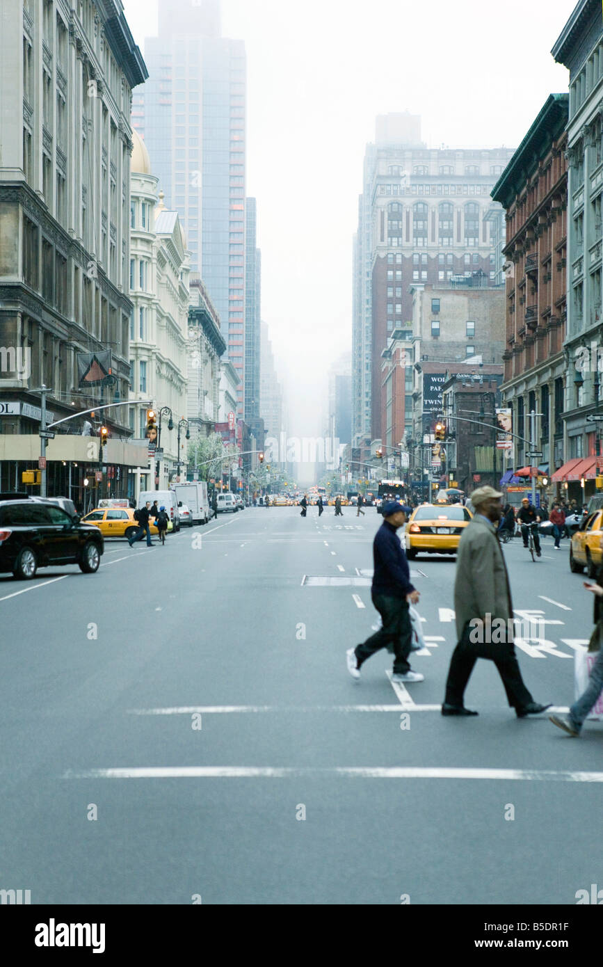 Fußgänger überqueren Straße in Zebrastreifen bei W 19th Street und 6th Avenue Chelsea in New Stockbild