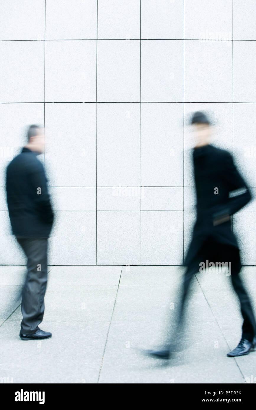 Zwei Männer einander vorbei, als sie auf dem Bürgersteig gehen Stockbild