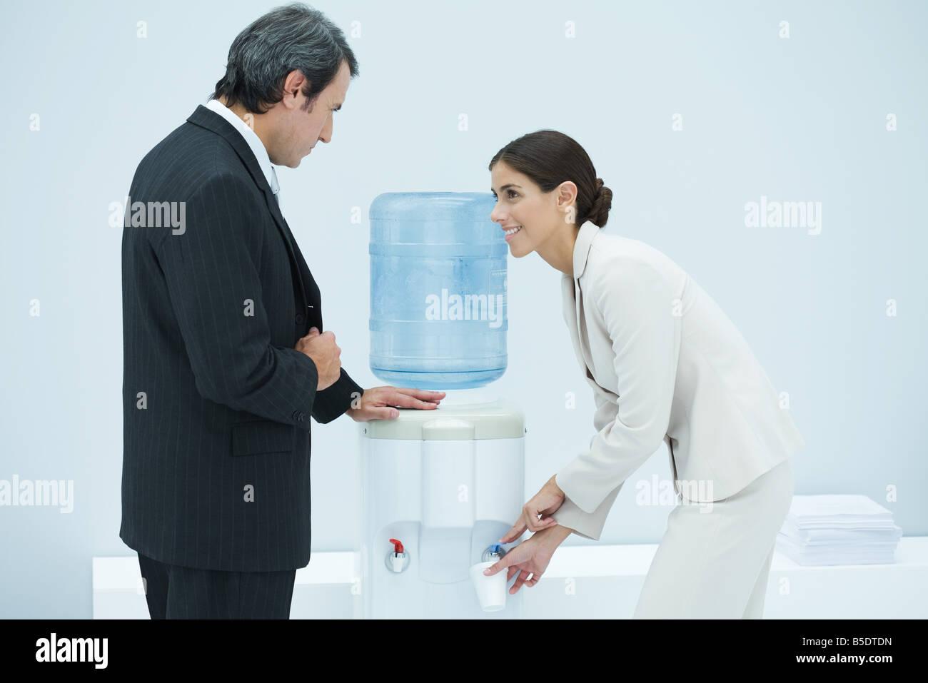 Zwei Profis im Chat neben Wasser-Kühler, Frau Einweg-Becher zu füllen Stockbild