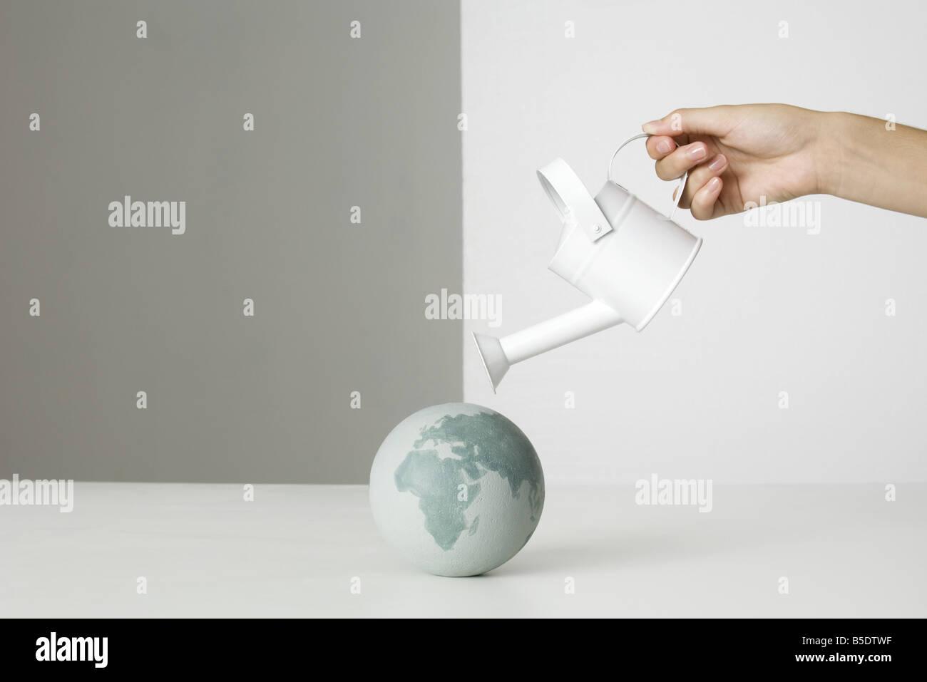Hand, die Gießkanne über kleine Weltkugel Stockbild