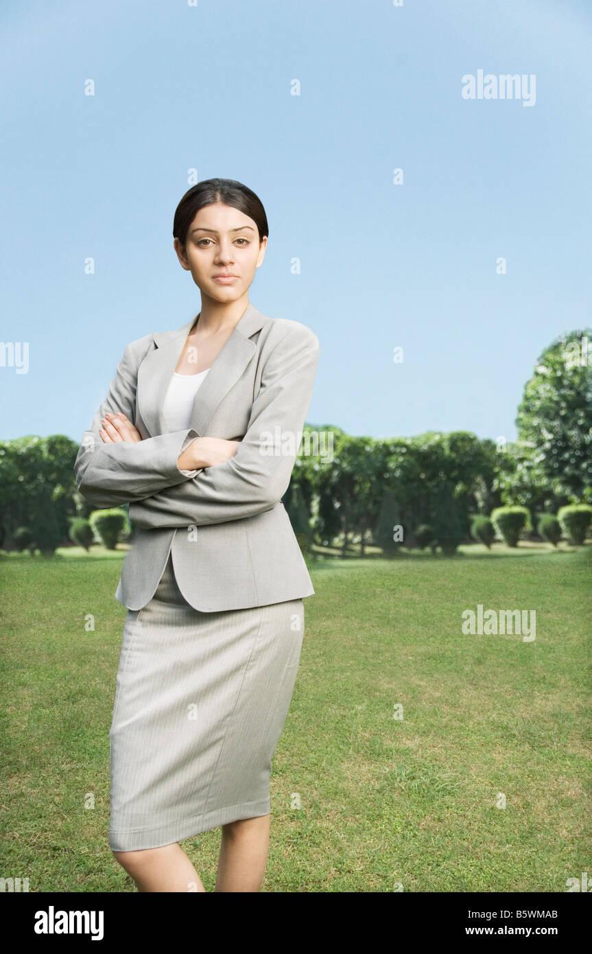 Geschäftsfrau, die mit ihren verschränkten Armen stehend Stockbild