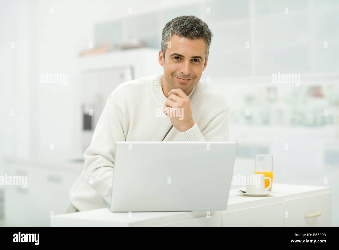 Mann mit Laptop-Computer in Küche, lächelnd in die Kamera Stockbild