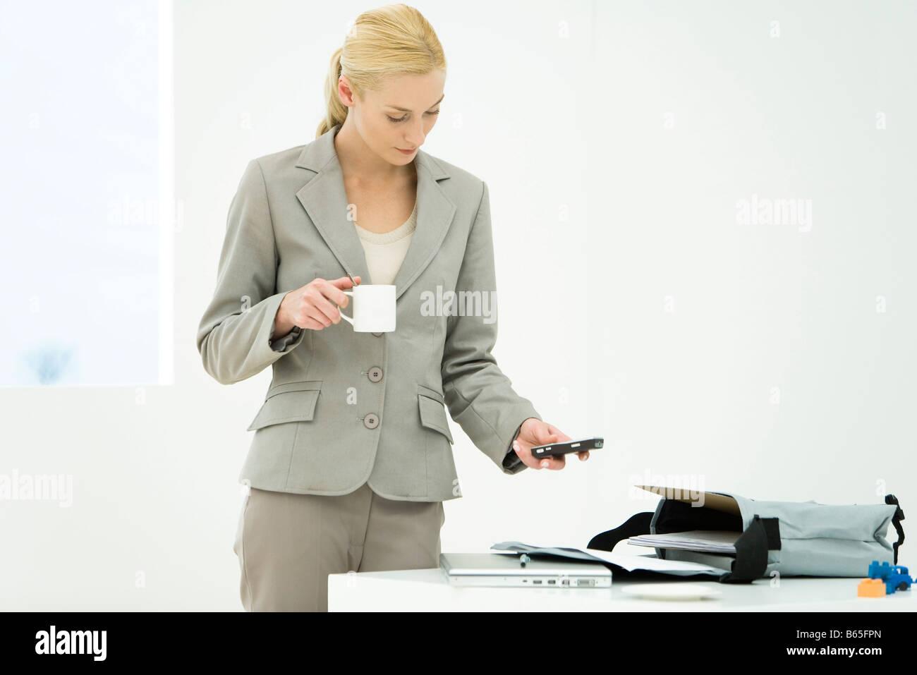 Berufstätige Frau mit Kaffeetasse, blickte, SMS-Nachrichten Stockbild