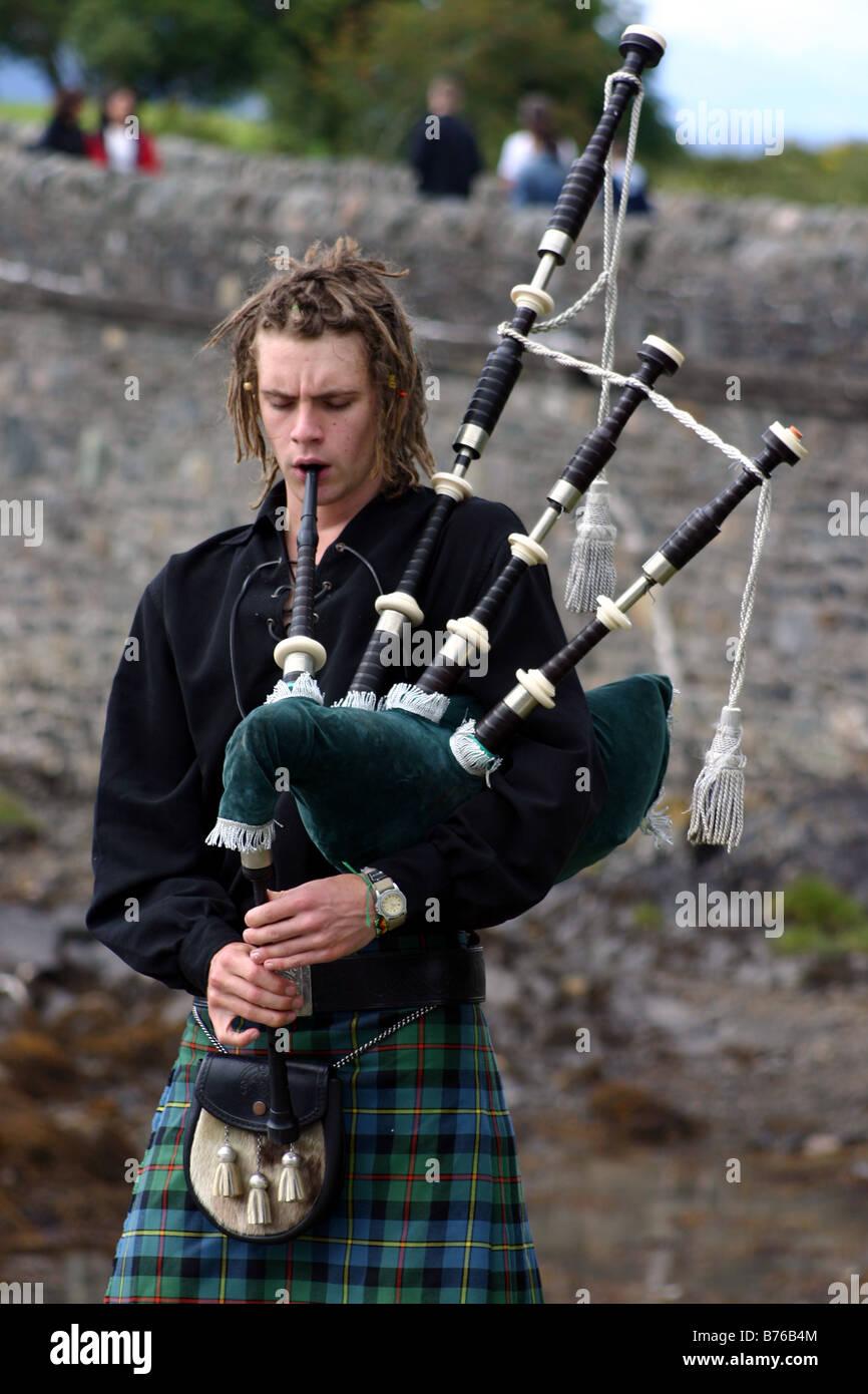 Traditionelle Mann im Kilt, Dudelsackspieler in Schottisches Hochland mit Dudelsack auf Eilean Donan Castle Stockbild