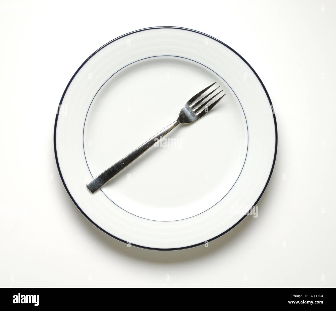 Ein runder weißer Teller mit einer Gabel Stockbild