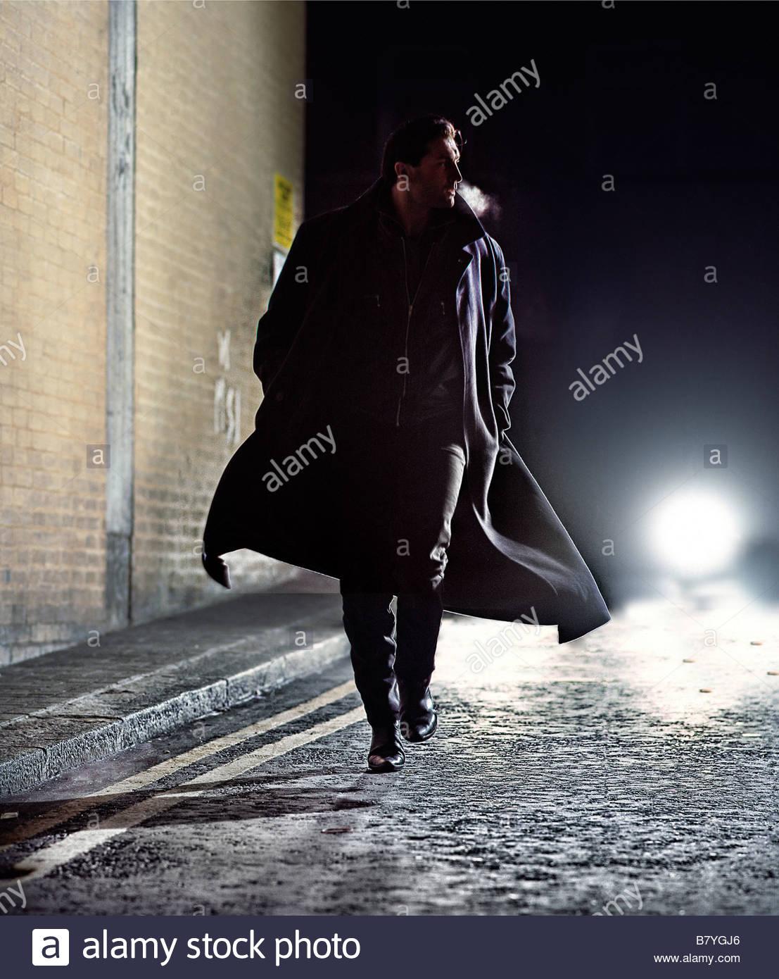 Mann im Mantel Tagfahrlicht Straße in der Nacht - Auto hinter Stockfoto
