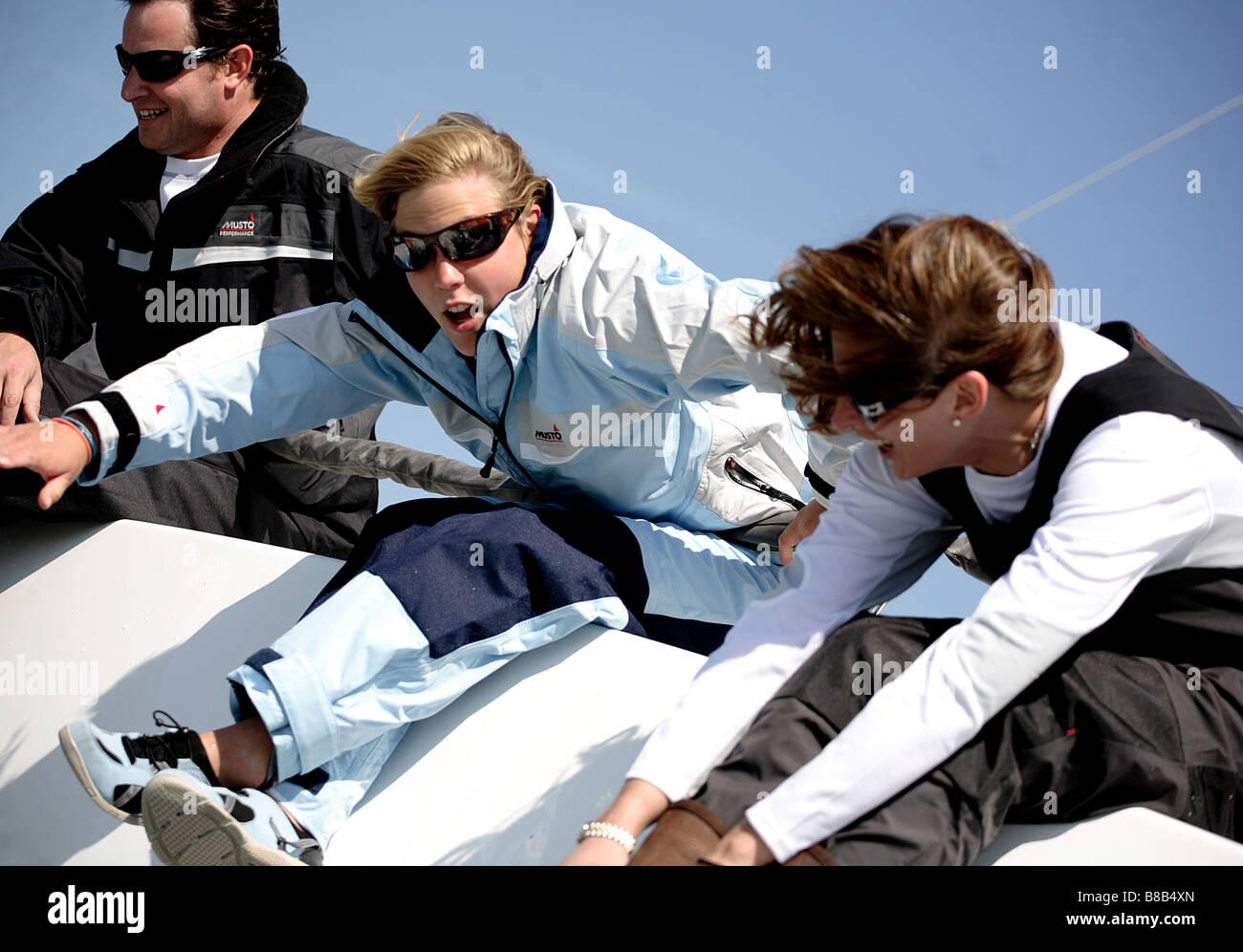 3 Erwachsene, 2 Frau und 1 Mann beugte sich über den Rand einer Yacht während des Rennens. Das Bild ist Stockbild