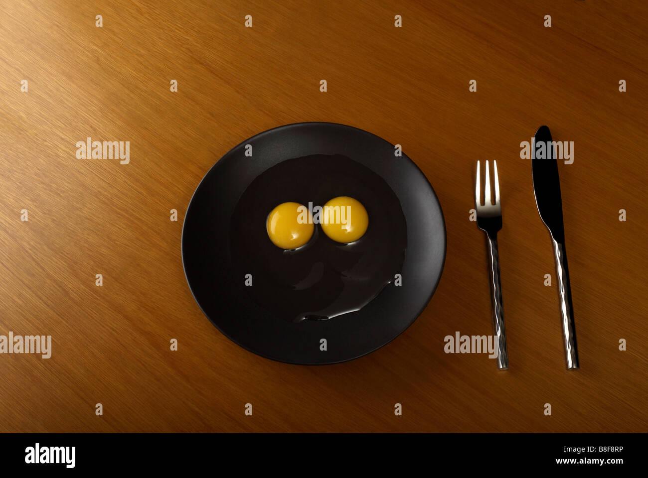 Rohen Eiern auf schwarzem Teller Stockbild