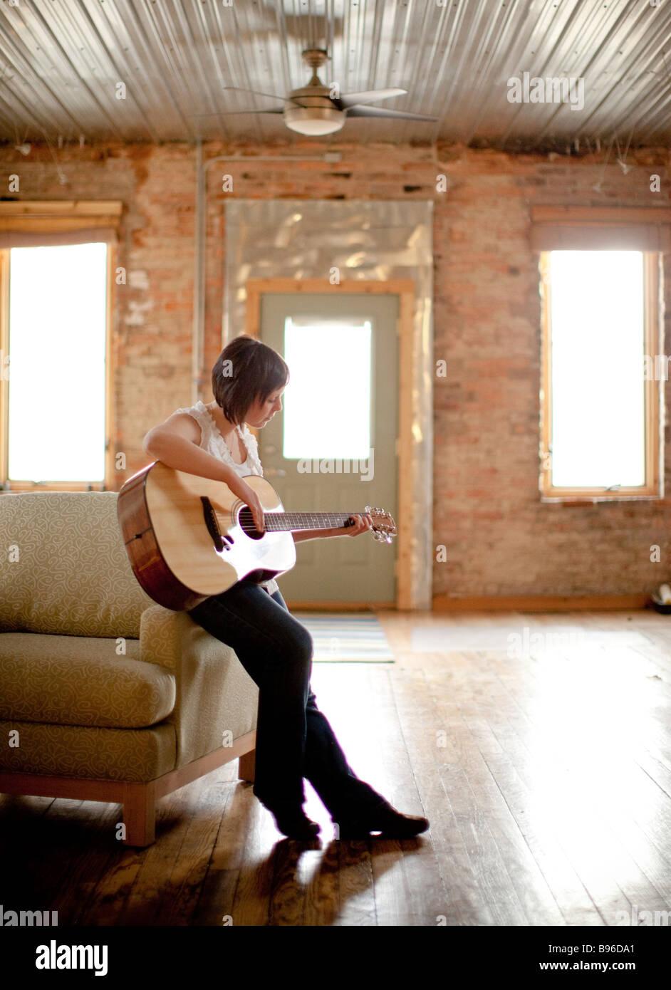 Junge Frau spielt Gitarre im urbanen Raum Stockbild