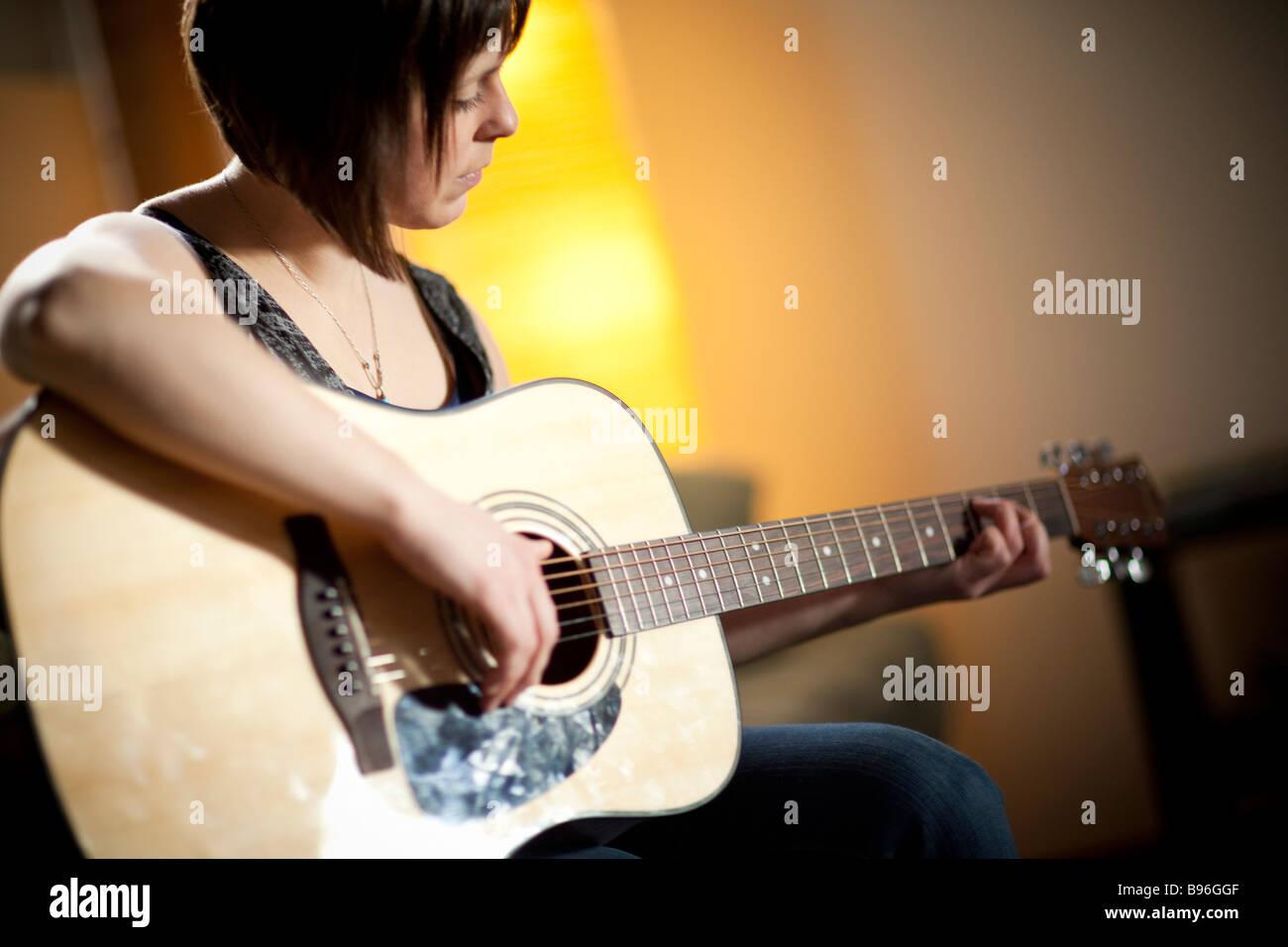 Junge Frau spielt Gitarre im urbanen loft Stockbild