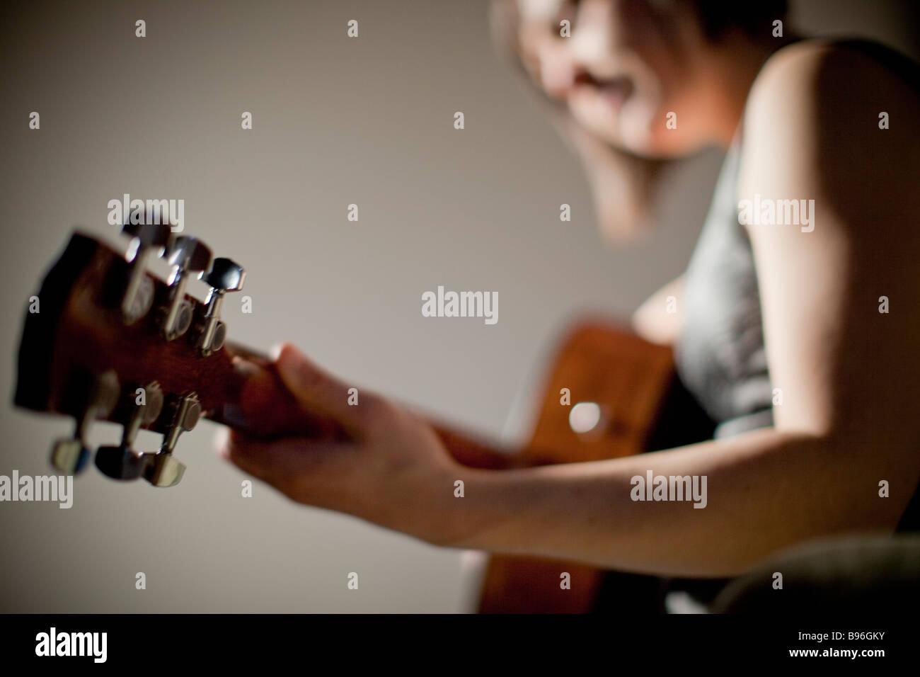 Junge Frau Gitarre spielen Stockbild