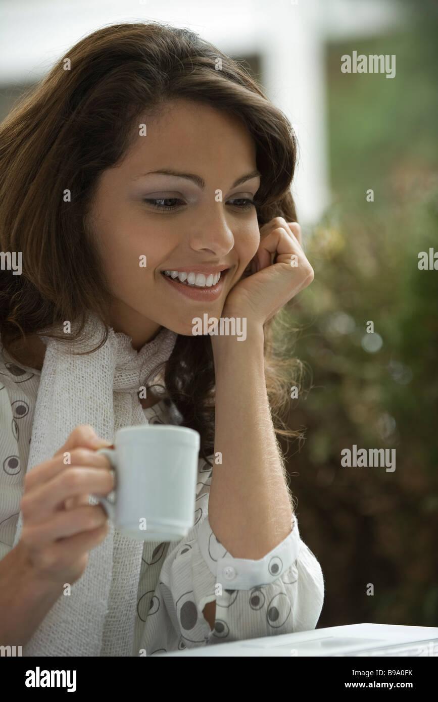 Junge Frau Kaffee trinken und mit Blick auf Laptop-computer Stockbild