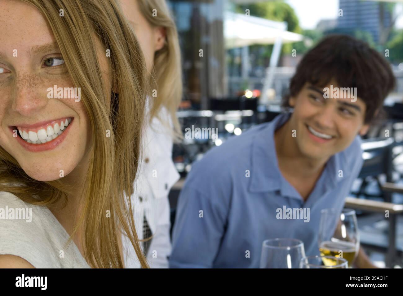 Junge Freunde am Straßencafé sitzen, über die Schultern schauen und Lächeln Stockbild