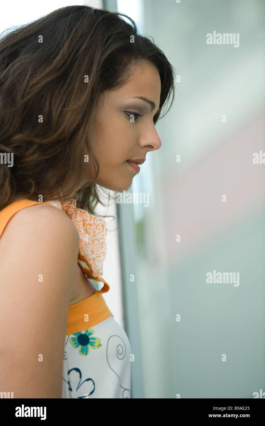 """Junge Frau, die im Fenster """"Profil"""" Stockbild"""