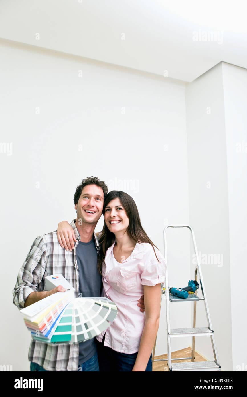 junges Paar, die Wahl der Farbe für die Wand in neue Wohnung mit Farbkarte Stockbild