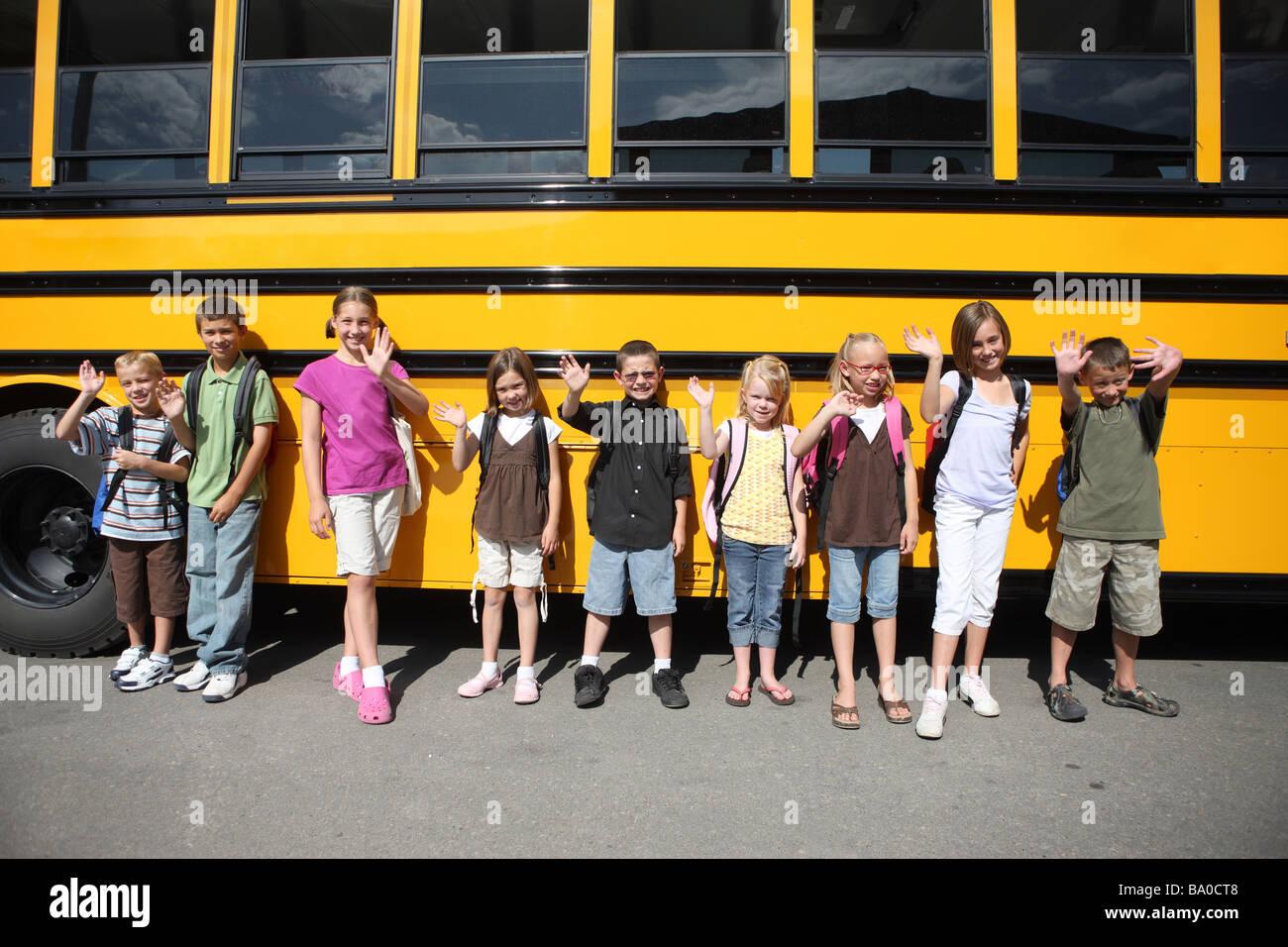 Gruppe von Schulkindern vor Schulbus Stockbild