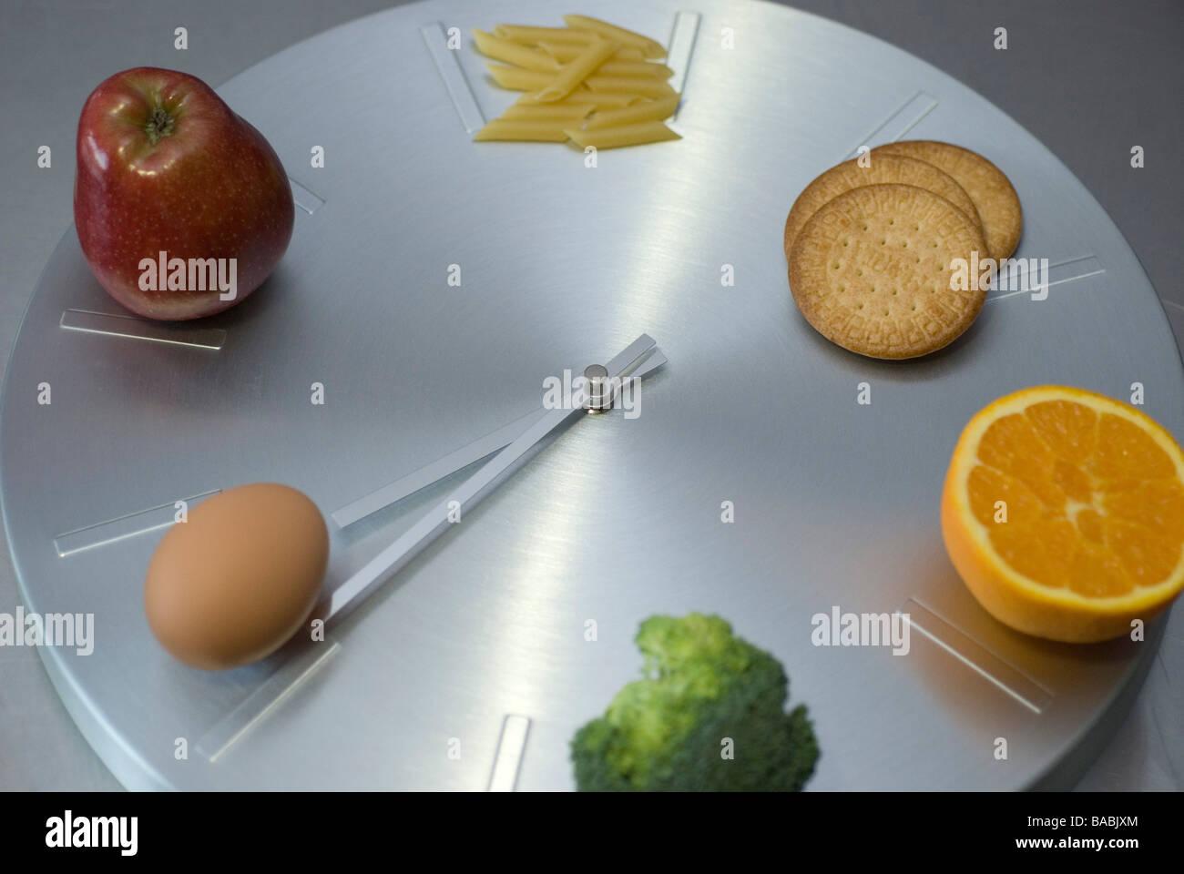 Uhr Essen Kontrolle-Nudeln, Kekse, Orange, Apfel, Ei und Brokkoli Stockbild