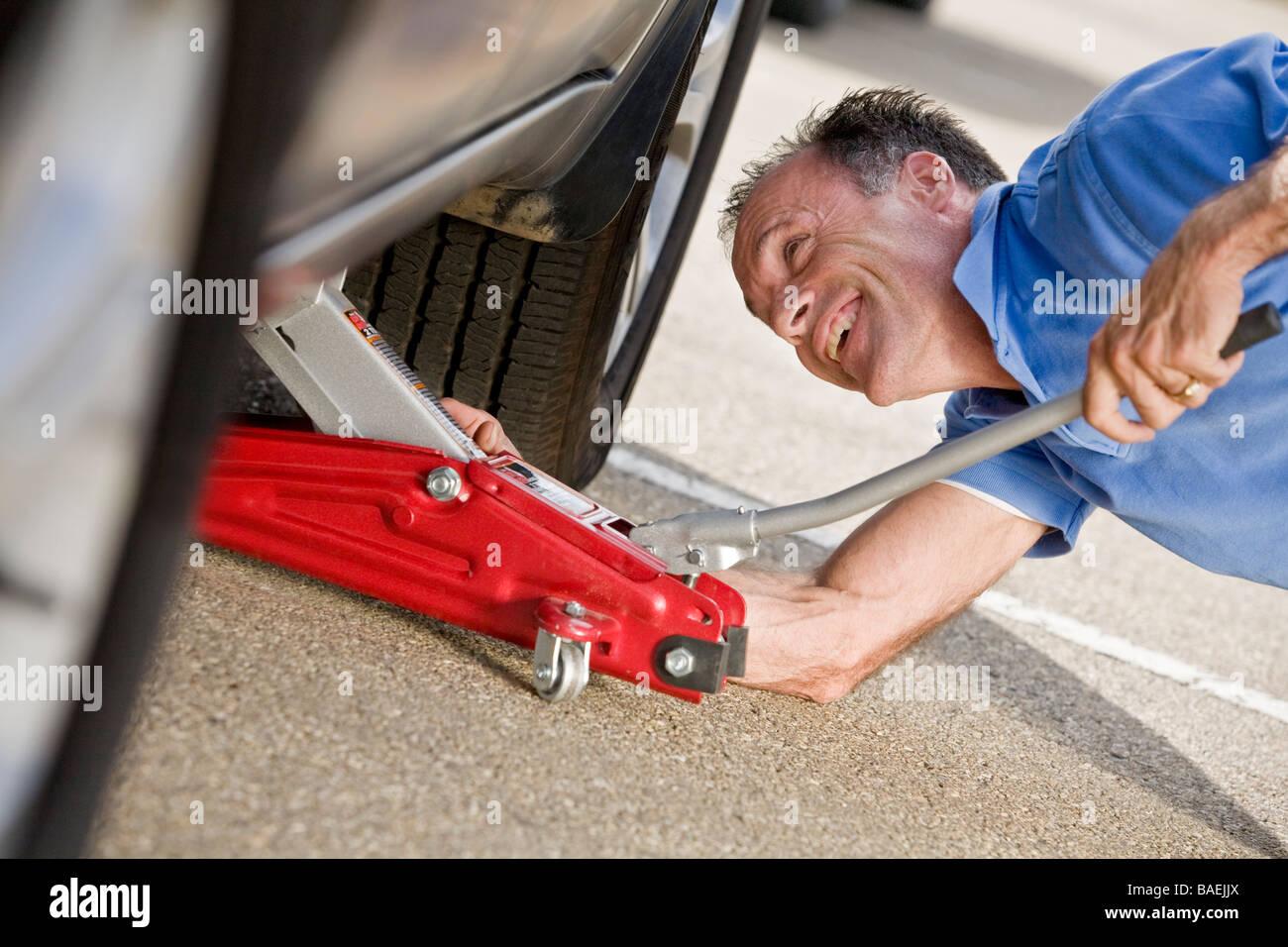 Man platziert einen Buben unter einem Fahrzeug Stockbild