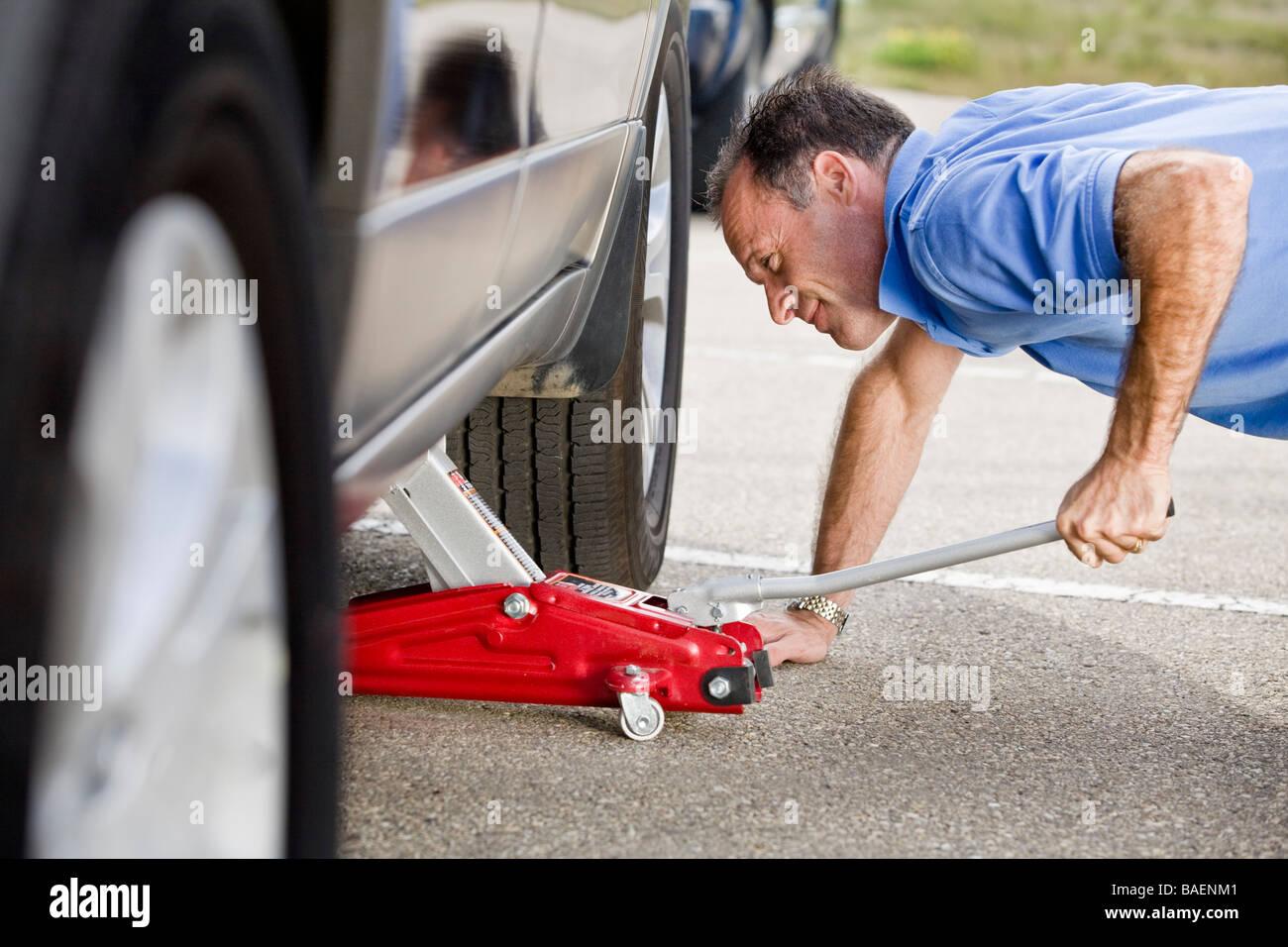 Mann ein Fahrzeug aufbocken Stockbild