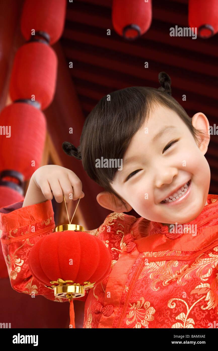 Junges Mädchen im Festival Chinese New Year Kleidung, lächelnd in die Kamera, mit chinesischer Lampion Stockbild