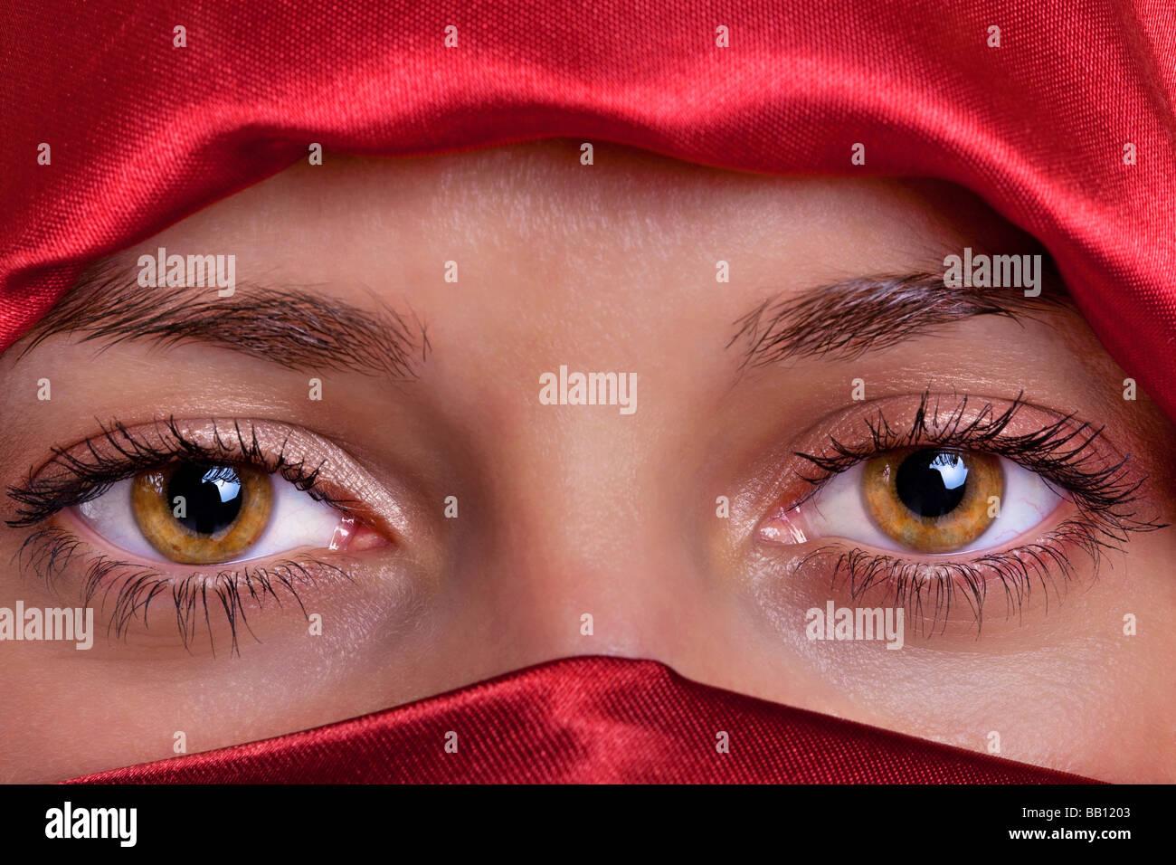 Nahaufnahme von ein paar schönen weiblichen braunen Augen, umrahmt von einem roten Seide Schleier Stockbild