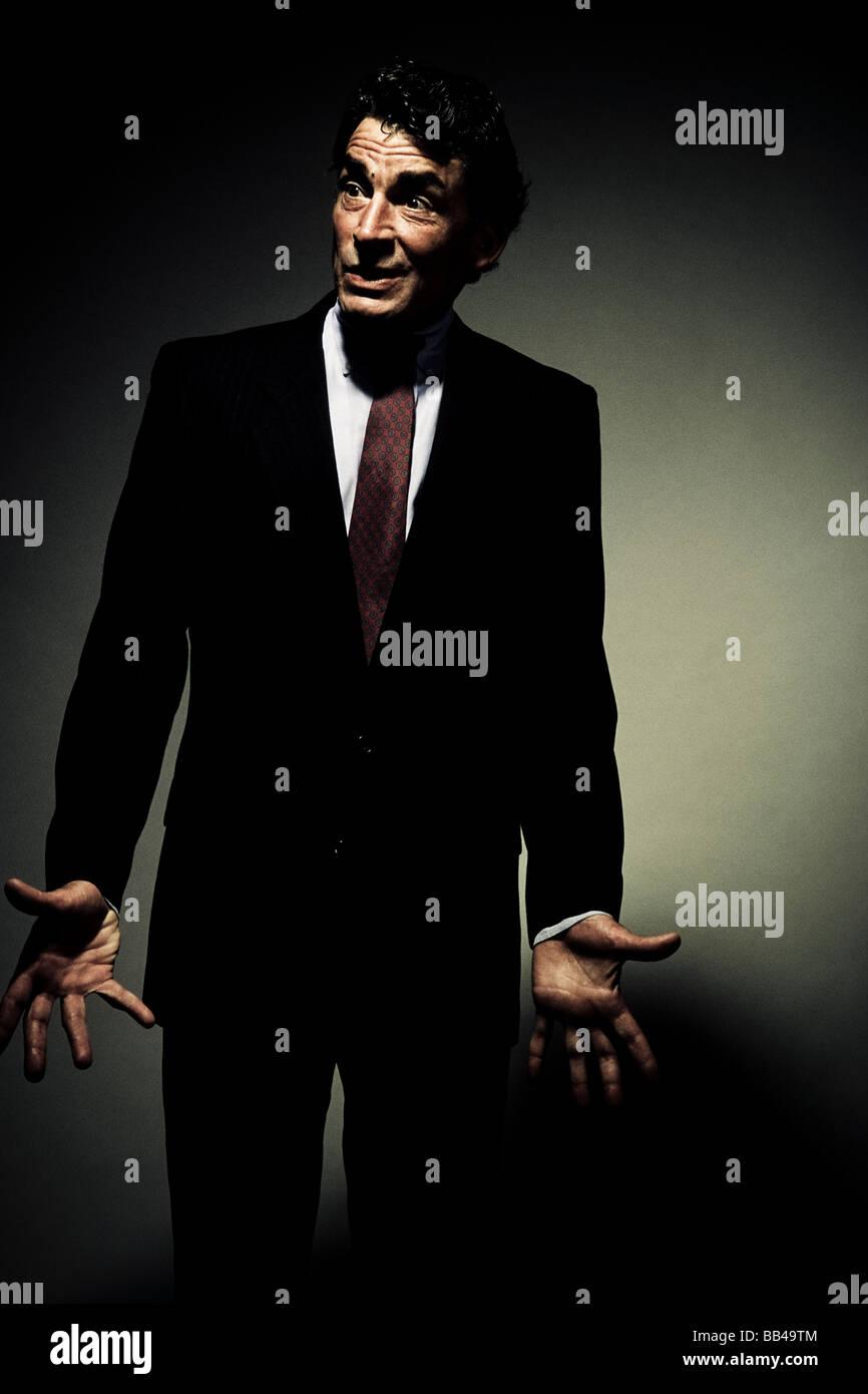 Vorderansicht eines reifen Mannes im Anzug, Blick auf die Seite mit den Handflächen aufgerissen frustriert Stockbild