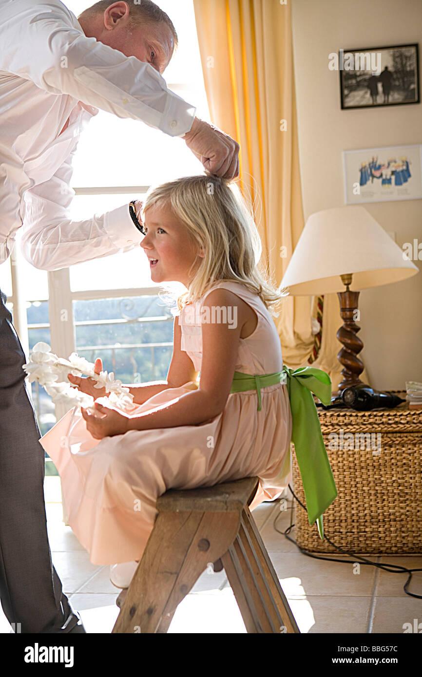 Vater bereitet Mädchen an den Haaren Stockfoto