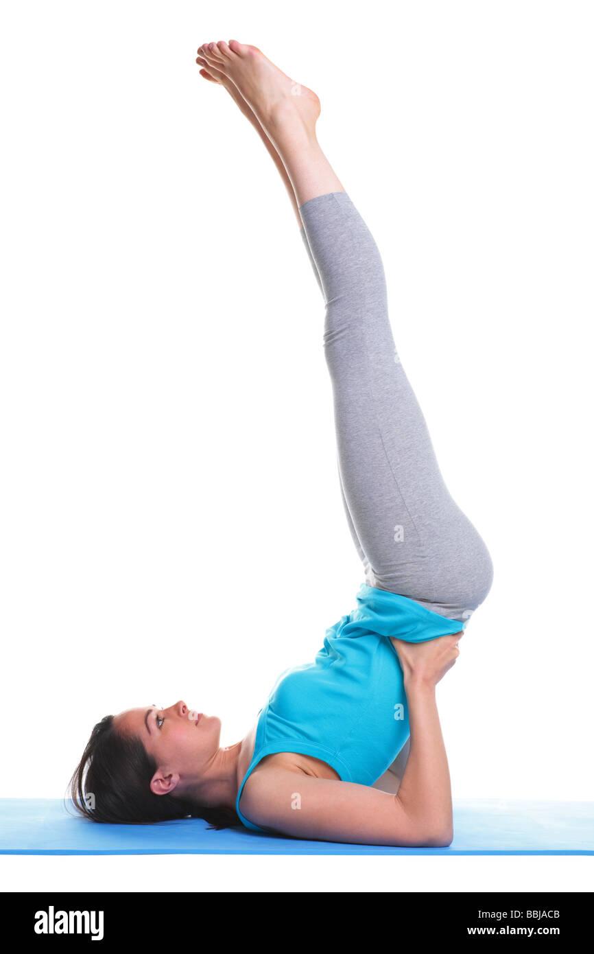 Brünette Frau tut ein Schulterstand auf einer Yogamatte isoliert auf weißem Hintergrund Stockbild