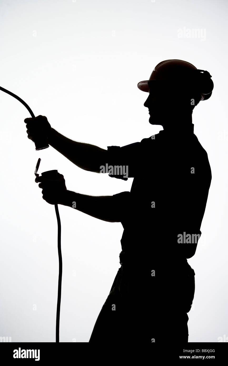 Ein Bauarbeiter mit einem Elektrokabel. Stockbild