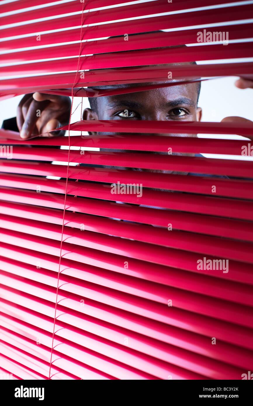 Afro amerikanische Geschäftsmann Blick durch rote Vorhänge Textfreiraum Stockbild