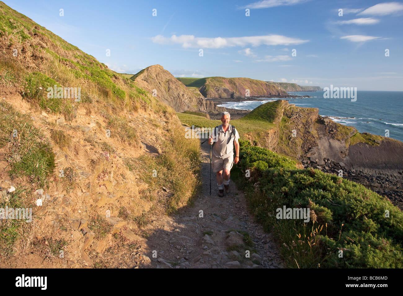 Applying Mann in den 50er Jahren zum Hartland Quay entlang Küsten Fußweg North Devon Heritage Coast England Stockbild