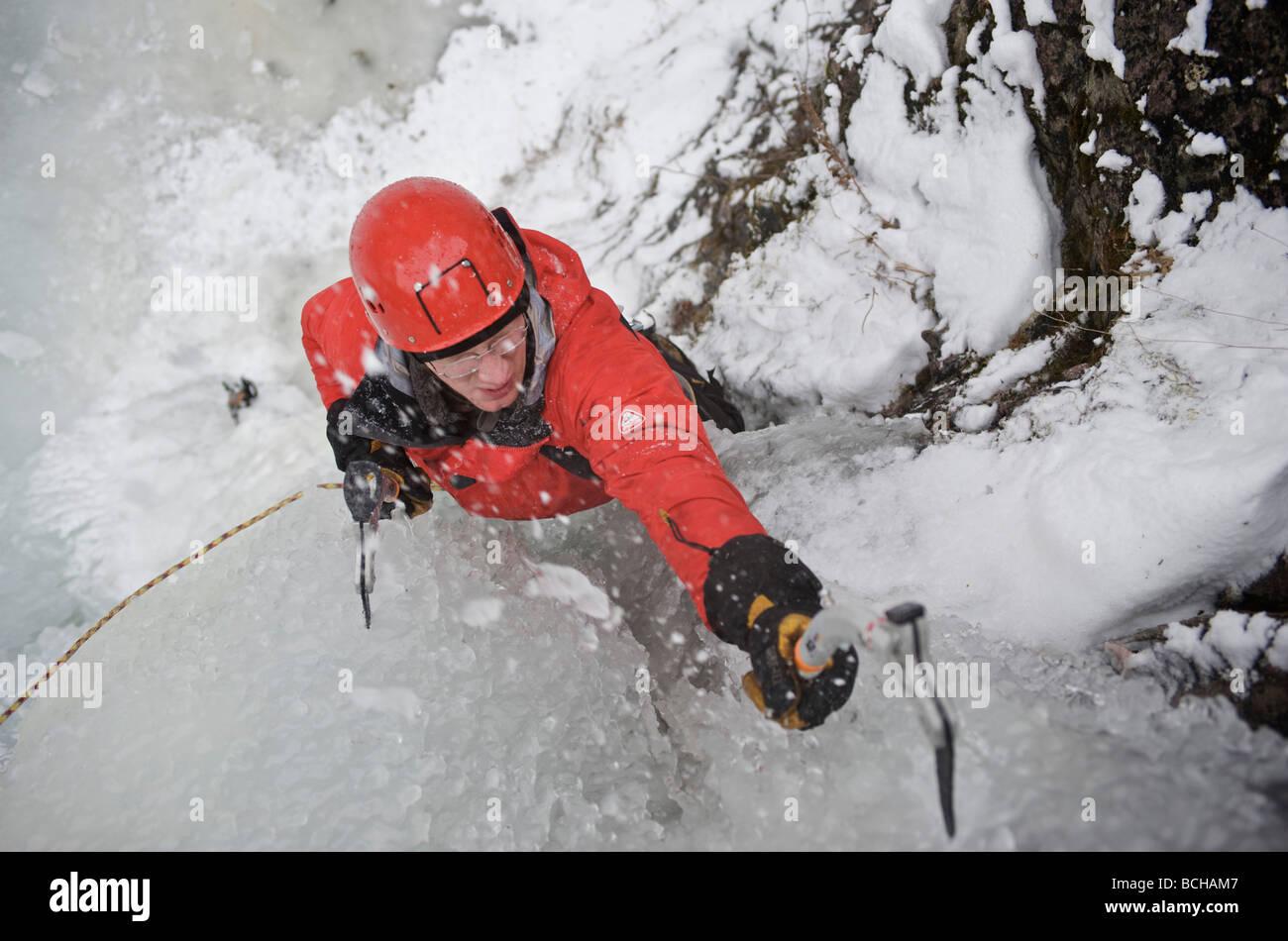 Eiskletterer klettert Ripple, eine beliebte Eisklettern über dem Eklutna-Fluss in den Chugach Mountains, Alaska Stockbild