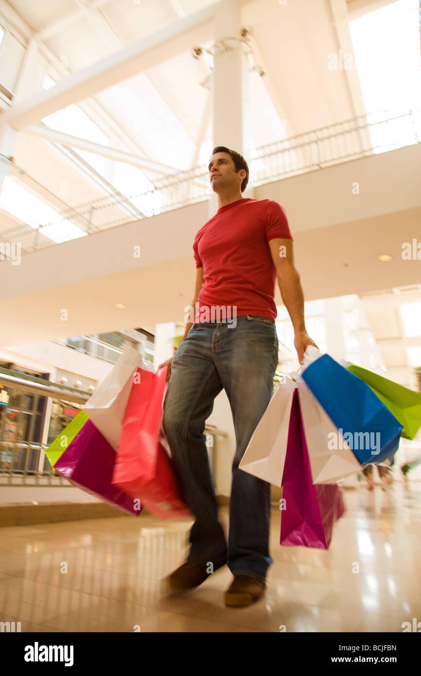 Kaukasischen Männchen Wandern im Einkaufszentrum Mall holding Taschen in verschiedenen Farben. Stockbild